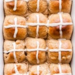 12 Hot Cross Buns in a white baking dish topped with white iced crosses.