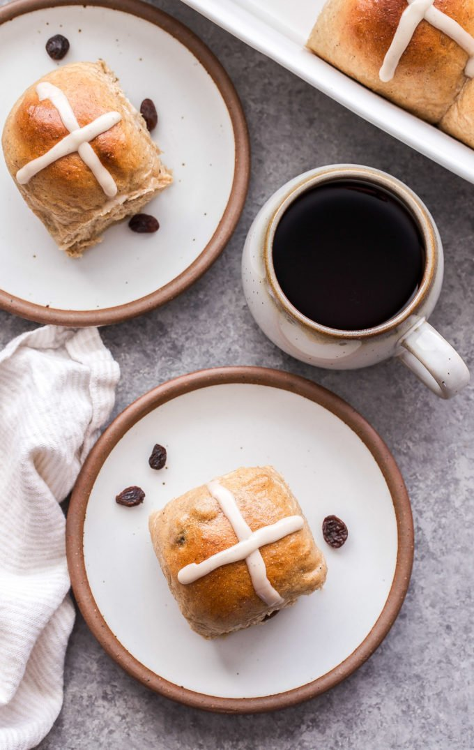 Two Hot Cross Buns on round white plates with a cup of coffee next to them.