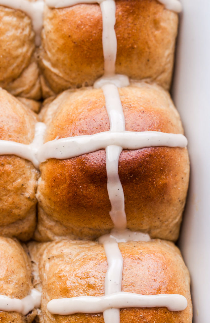 Closeup of a Hot Cross Bun topped with a white icing cross.