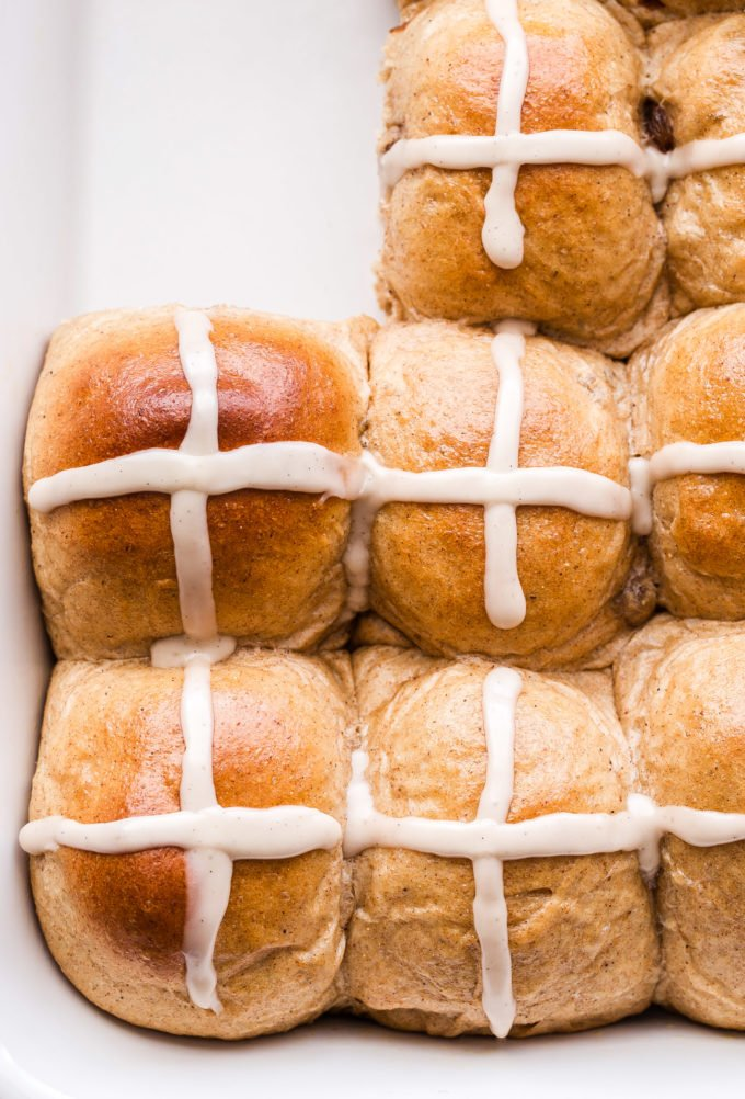 Hot Cross Buns in white baking dish with two buns removed.