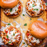 Four Italian Sloppy Joes on a sheet pan. Two are open faced and the other two have the top bun partially off.