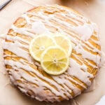 Overhead photo of a round Lemon Yogurt Cake drizzled with white glaze and topped with three lemon slices.