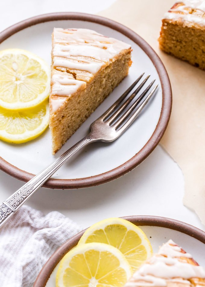 A slice of Lemon Yogurt Cake on a white round plate with a fork and two lemon slices.