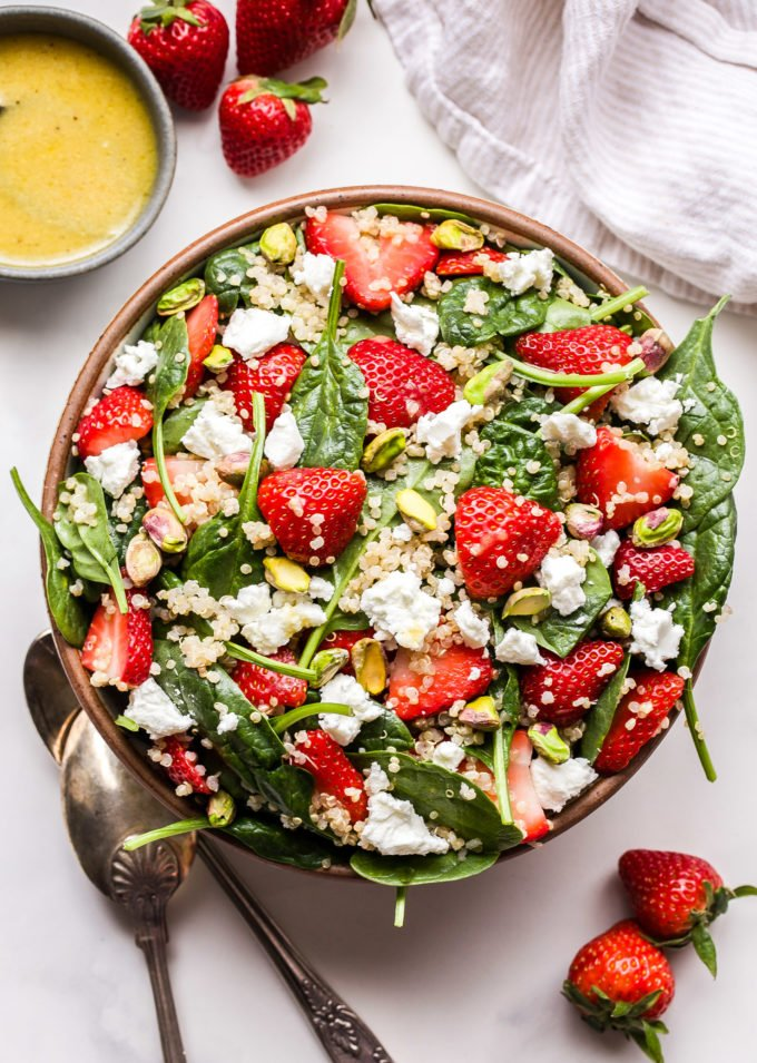 Strawberry Spinach Quinoa Salad with goat cheese and pistachios in a white serving bowl with serving spoons next to the bowl and lemon vinaigrette in a bowl behind the salad.