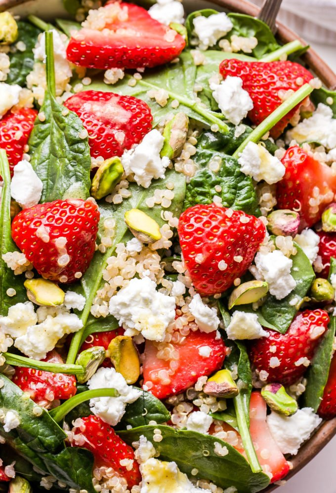Closeup photo of Strawberry Spinach Quinoa Salad in serving bowl with goat cheese and pistachios.