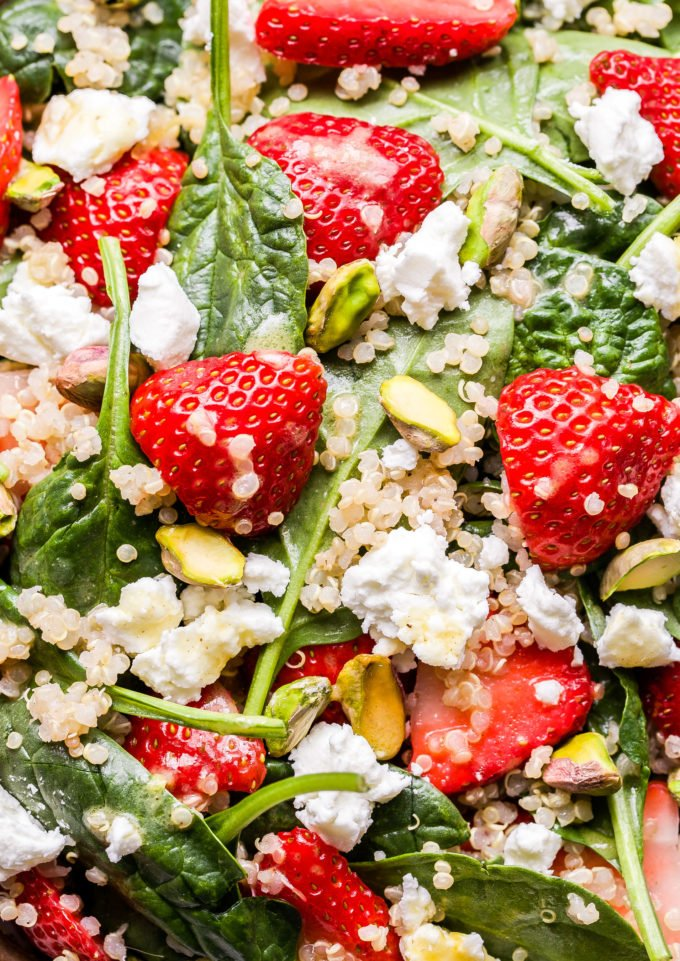 closeup photo of Strawberry Spinach Quinoa Salad with goat cheese crumbles and pistachios.