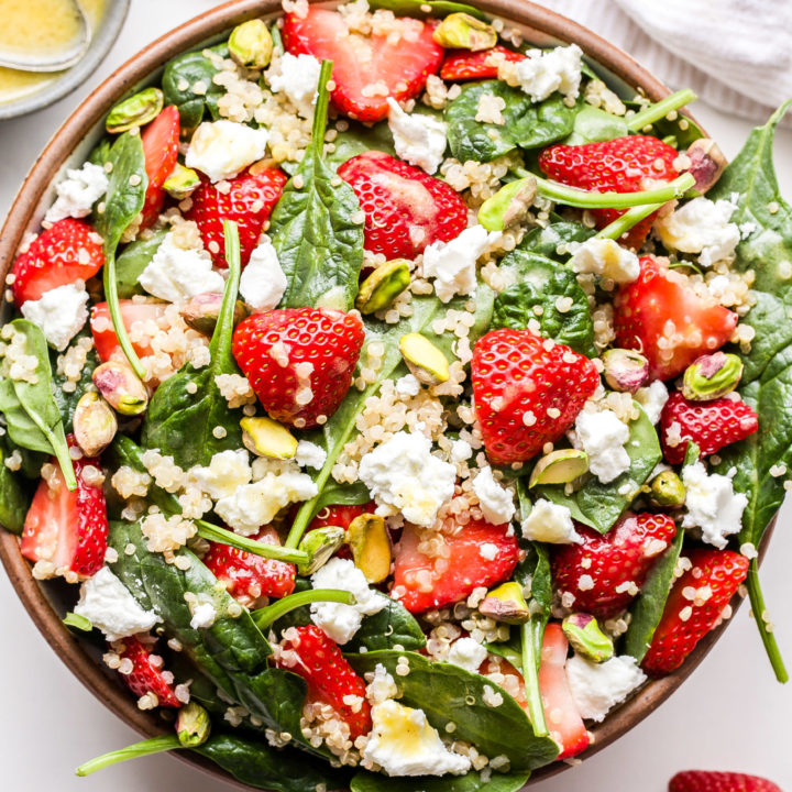 Strawberry Spinach Quinoa Salad with goat cheese and pistachios in a serving bowl.