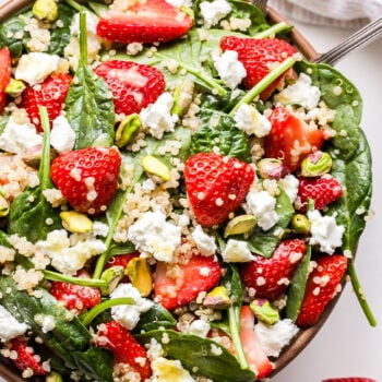 Strawberry Spinach Quinoa Salad with goat cheese and pistachios in a serving bowl with spoons.