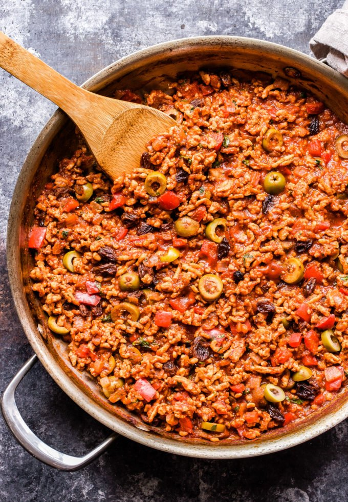 Turkey Picadillo with green olive and raisins in a skillet with a wooden spoon.