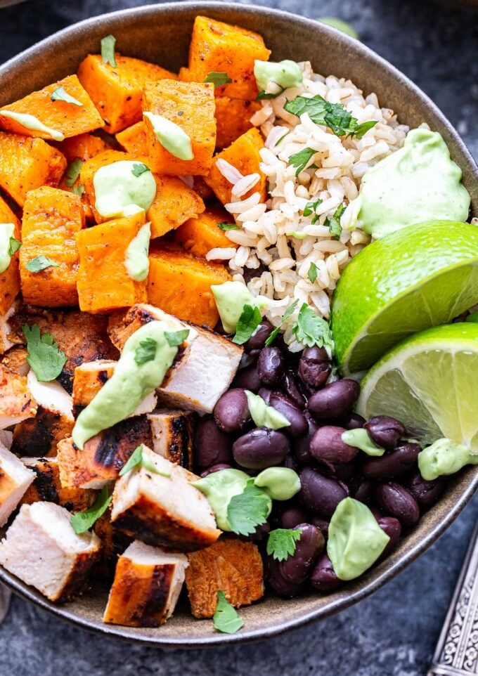 Overhead photo of Chili Lime Chicken Burrito Bowl with sweet potatoes, black beans, rice and topped with avocado sauce.