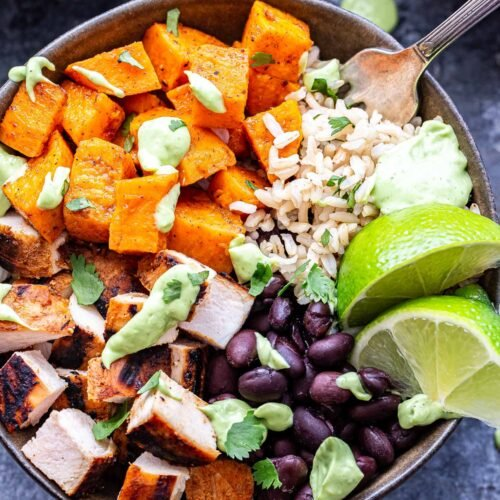 Closeup of Chili Lime Chicken Burrito Bowl with sweet potatoes, black beans, rice and topped with avocado sauce. A fork is in the bowl.