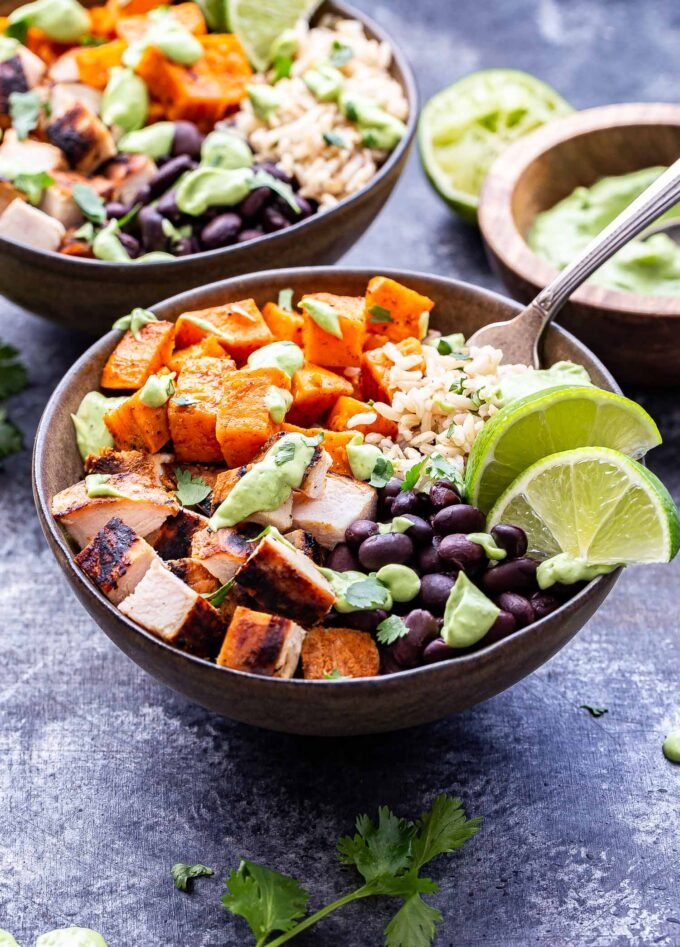 Chili Lime Chicken Burrito Bowl with sweet potatoes, black beans, rice and topped with avocado sauce.