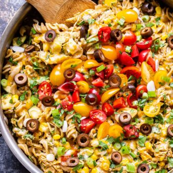 Creamy Chicken Enchilada Pasta in pan with a wooden serving spoon. Topped with tomatoes, olives, green onions and cilantro.
