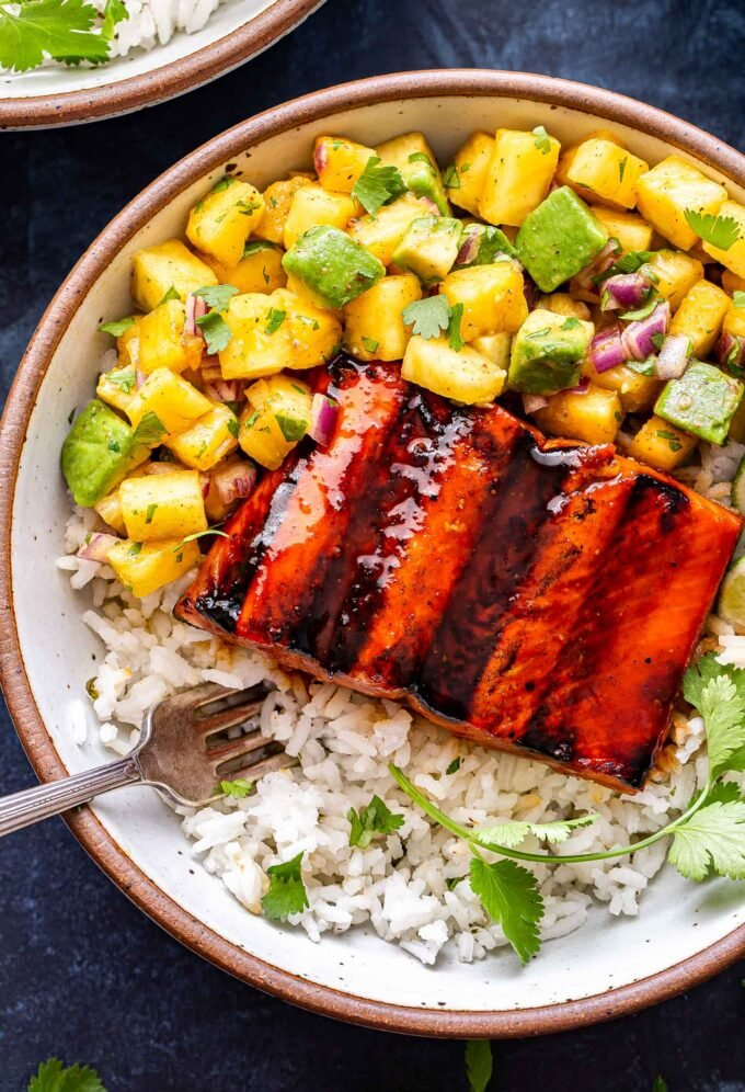 Overhead photo of Honey Sriracha Salmon with Pineapple Avocado Salsa in a white bowl on top of rice with a fork in the bowl.