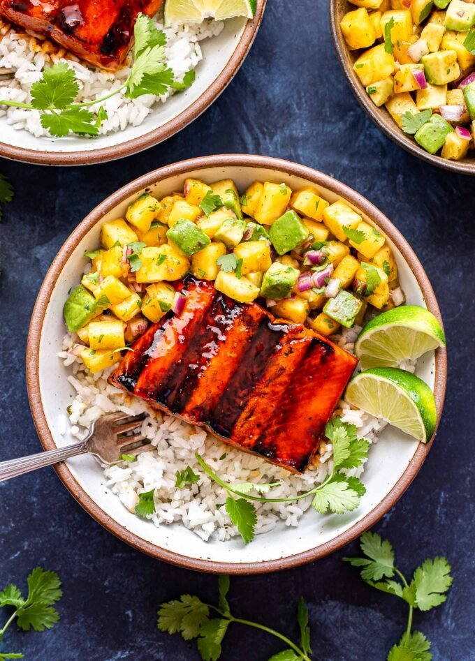 Overhead photo of two white bowls filled with rice and topped with Honey Sriracha Salmon with Pineapple Avocado Salsa. Bowl of salsa next to them.