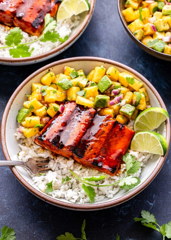 Honey Sriracha Salmon with Pineapple Avocado Salsa in a white bowl on top of rice with lime wedges next to it. A bowl of salsa is behind it.