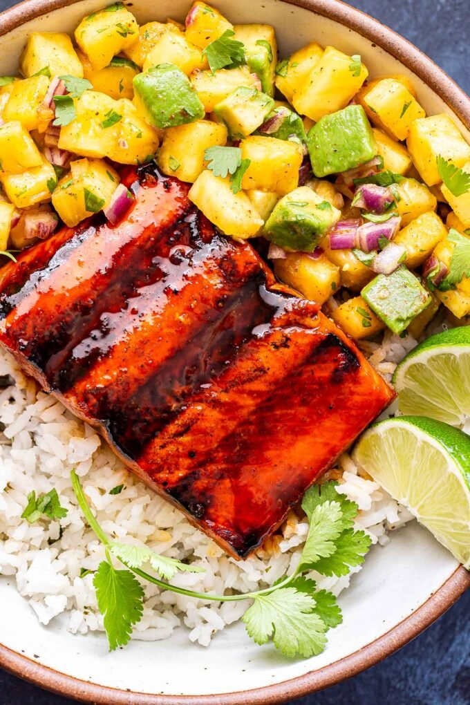 Closeup photo of Honey Sriracha Salmon with Pineapple Avocado Salsa served over rice in a white bowl.