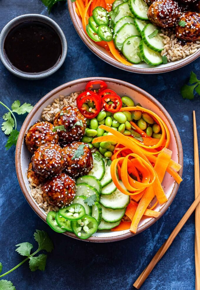 Overhead photo of two Asian Turkey Meatball Bowls and a small dish with sauce in it. Bowls filled with rice, meatballs, edamame, carrot ribbons and cucumber slices.