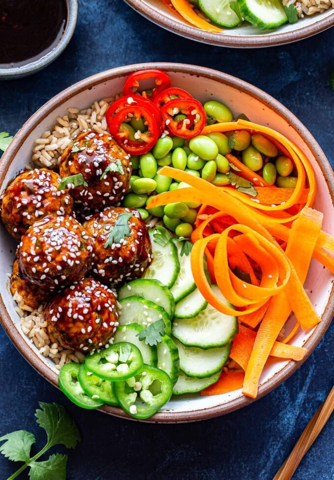 Overhead photo of Asian Turkey Meatball Bowl with chopsticks next to the bowl. Bowl filled with rice, cucumbers, carrots, edamame, jalapenos and five meatballs.