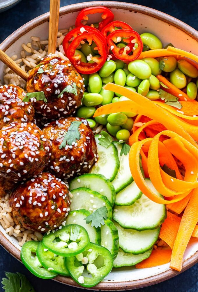 Overhead closeup photo of Asian Turkey Meatball Bowl filled with four meatballs, cucumber slices, jalapeno slices, edamame, and carrot ribbons.