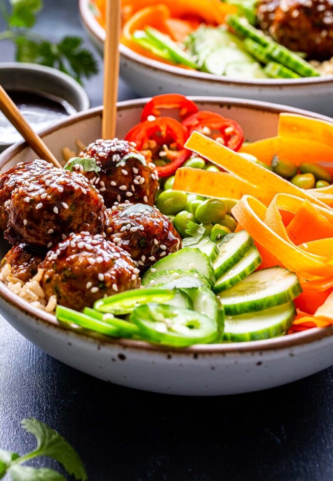 Front angle photo of Asian Turkey Meatball Bowl. White bowl filled with rice and topped with meatballs, cucumbers, carrots and edamame. Meatballs sprinkled with sesame seeds.