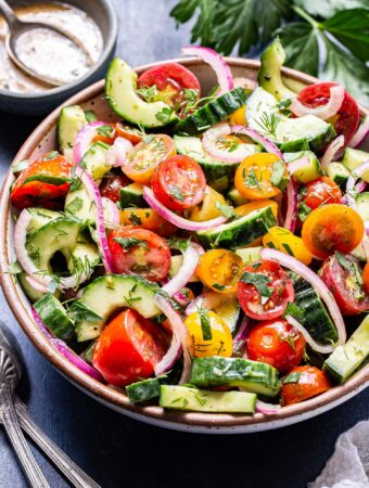 Cucumber tomato salad with sliced red onions and herbs in a serving bowl. Small bowl of vinaigrette with a spoon in it behind the salad and two serving spoons next to it.