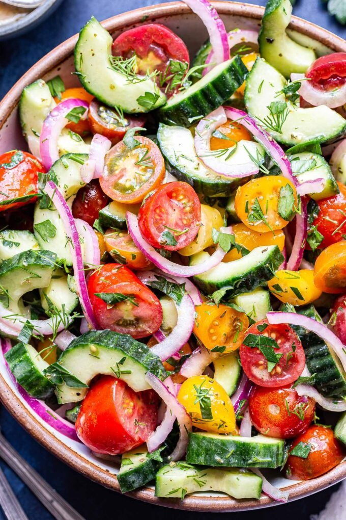 Closeup photo of Cucumber Tomato Salad in white bowl with red onions and chopped herbs.