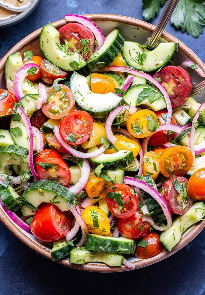 Cucumber tomato salad with red onions and herbs in a white serving bowl with two spoons in the bowl.