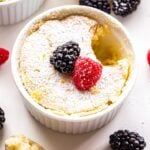 White ramekin with a lemon pudding cake in it. Topped with a raspberry and blackberry. A scoop of the cake is scooped out and on a spoon next to the ramekin.