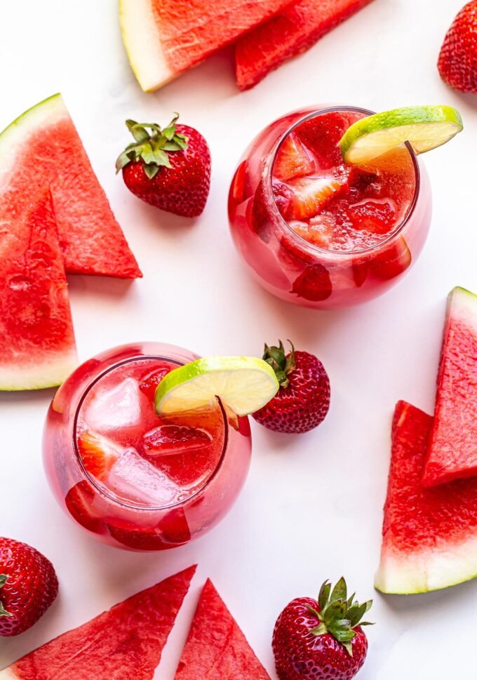 Overhead photo of two glasses of Strawberry Watermelon Rosé Sangria with a round lime slice on the edge of the glass. Watermelon slices and strawberries surrounding the glass.