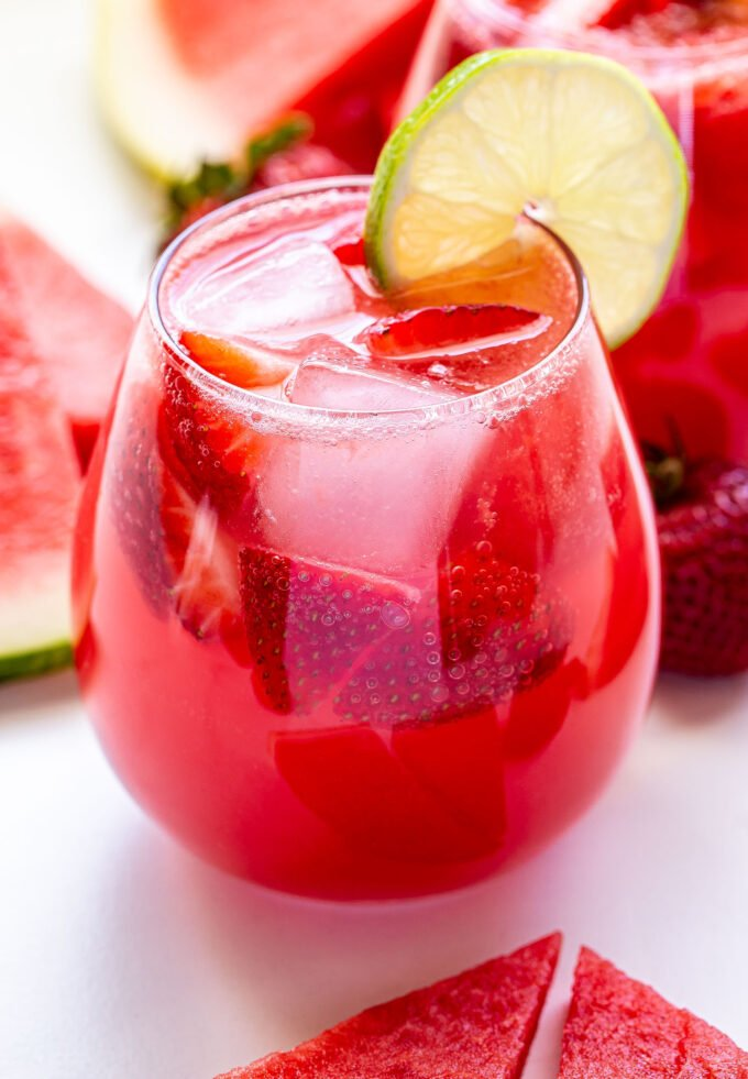 Closeup front facing photo of A glass of Strawberry Watermelon Rosé Sangria with a round lime slice on the edge of the glass. Watermelon slices and strawberries surrounding the glass.