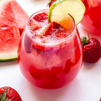 A glass of Strawberry Watermelon Rosé Sangria with a round lime slice on the edge of the glass. Watermelon slices and strawberries surrounding the glass.