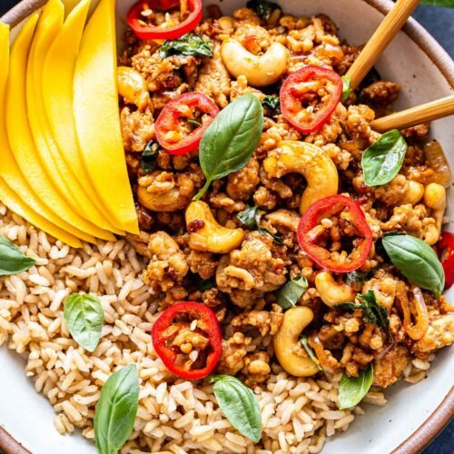 Closeup overhead photo of Thai Basil Chicken on top of rice in a white bowl with chopsticks. Garnished with mango slices, sliced Thai chiles and basil leaves.