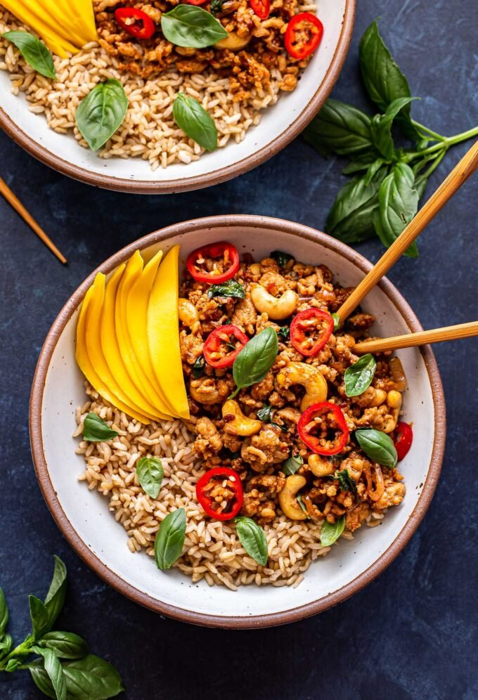 Overhead photo of two Thai Basil Chicken Bowls. Topped with slices of mango and chopsticks in the bowl.