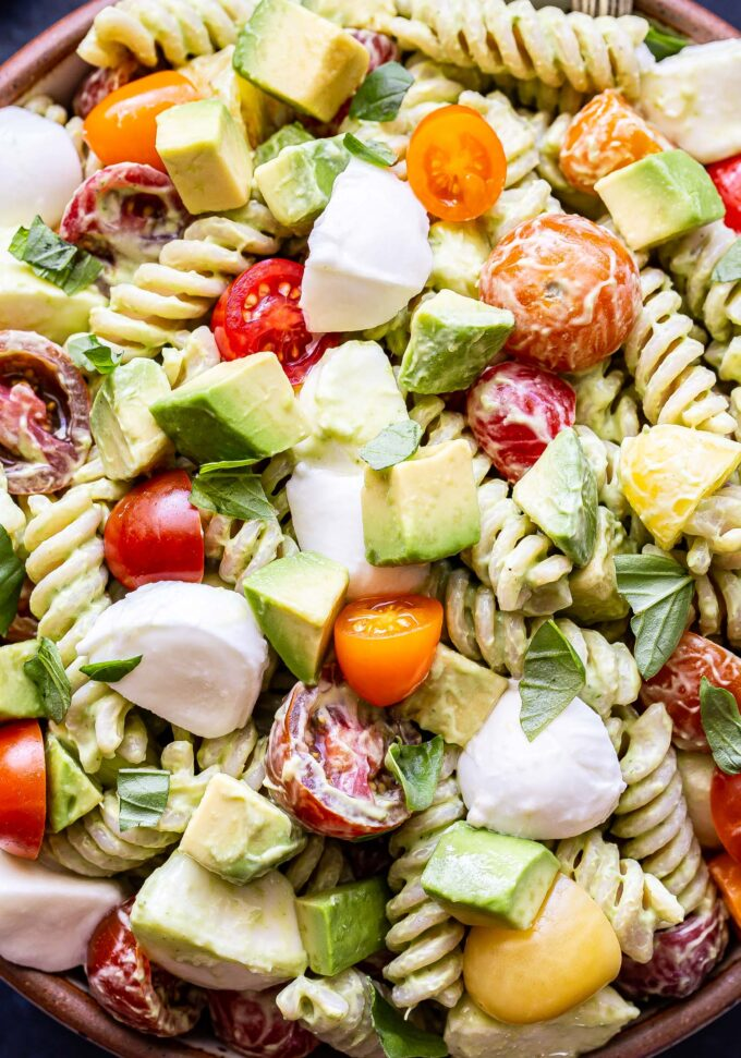 Closeup photo of pasta salad with rotini pasta, tomatoes, mozzarella and avocado chunks all coated in an creamy avocado dressing.