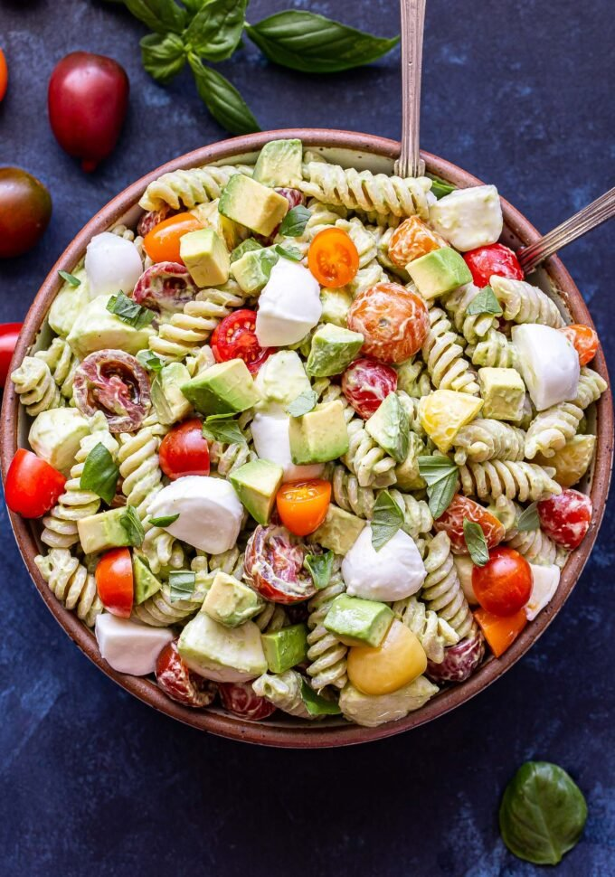 Overhead photo of Tomato Avocado Pasta Salad with mozzarella chunks and basil leaves in a white bowl with two spoon.