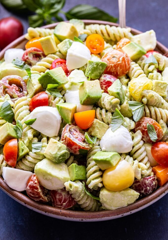 Tomato Avocado Pasta Salad with mozzarella chunks and basil leaves in a white bowl with a spoon. Basil leave and a tomato behind the bowl.