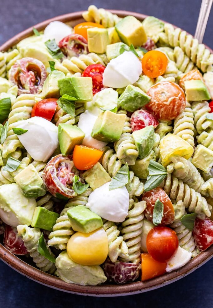 Tomato Avocado Pasta Salad with mozzarella chunks and basil leaves in a white bowl with a spoon.
