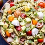 Overhead photo of Tomato Avocado Pasta Salad with chunks of fresh mozzarella and basil in a bowl with a spoon.