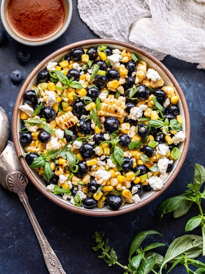Overhead photo of Blueberry Corn Feta Salad with basil in a serving bowl with spoons next to it, a small bowl of dressing behind it and basil leaves to the side.