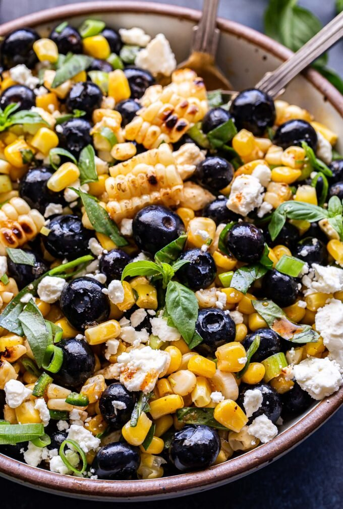 Closeup photo of Blueberry Corn Feta Salad with basil in a white serving bowl with serving spoons in the bowl.