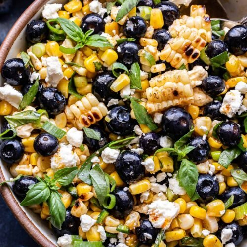 Overhead photo of Blueberry Corn Feta Salad with basil in a white serving bowl.
