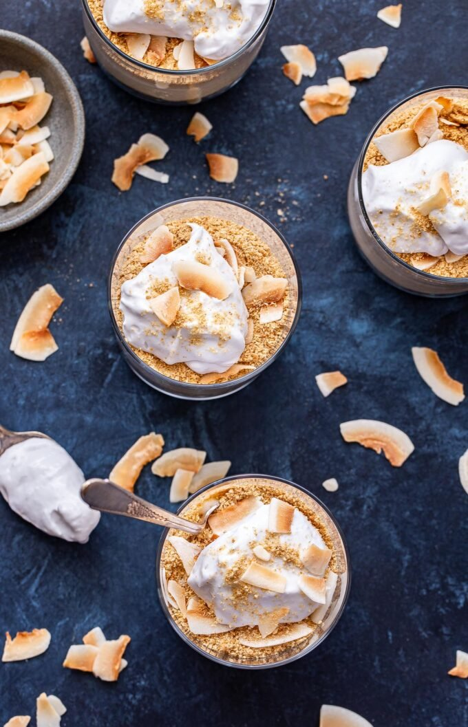 Overhead photo of four Coconut Cream Pie Parfaits with toasted coconut flakes scattered around them and a small bowl of coconut flakes in the background.