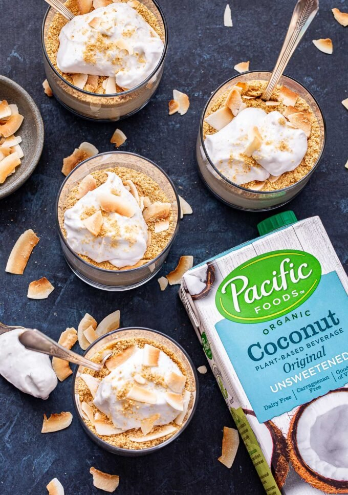 Overhead photo of four Coconut Cream Pie Parfaits in glasses with toasted coconut scattered around them and a box of Pacific Foods coconut beverage on the right side.