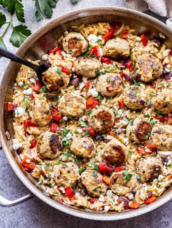 Metal skillet filled with Greek Meatballs and Orzo and a black serving spoon.