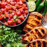 Overhead photo of grilled honey lime chicken with a bowl of watermelon salsa, squeezed lime halves and jalapaños behind the chicken. A bunch of cilantro next to the chicken.