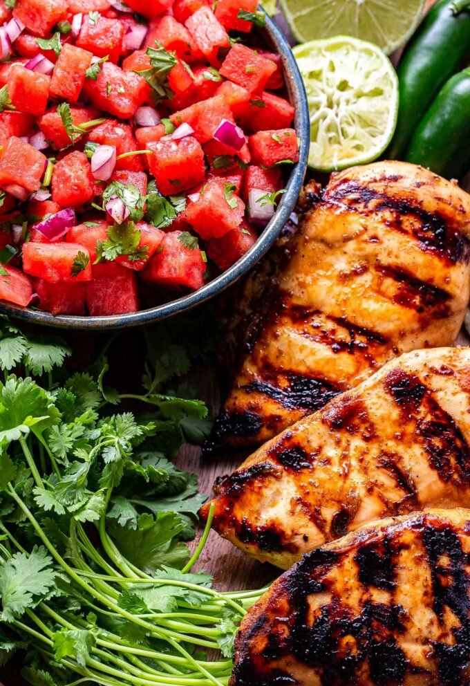 Overhead photo of grilled honey lime chicken with a bowl of watermelon salsa and squeezed lime halves behind the chicken. A bunch of cilantro next to the chicken.