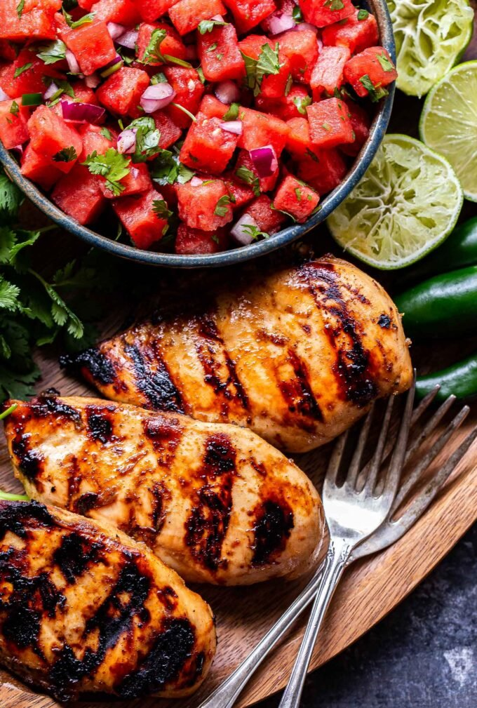 Overhead photo of grilled honey lime chicken with a bowl of watermelon salsa behind the chicken and squeezed lime halves, jalapeños and forks next to the chicken.