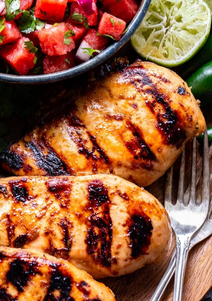 Closeup photo of grilled honey lime chicken with a bowl of watermelon salsa in the background and a squeezed half of a lime.
