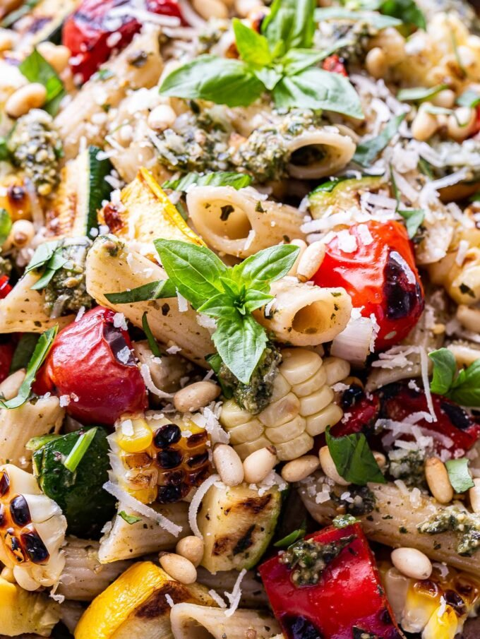 Closeup photo of grilled zucchini, summer squash, tomatoes, corn and pasta. Coated in pesto and garnished with basil, parmesan cheese and pine nuts.